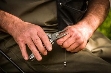 Man using multi-tool to set up fishing line