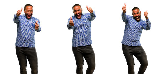 African american man with beard stand happy and positive with thumbs up approving with a big smile expressing okay gesture