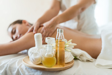 Bottle of essential oil on a wooden tray. background Young beautiful Asian woman relaxing in the spa massage