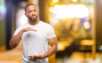 African american man with beard holding something, size concept at night