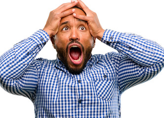African american man with beard stressful keeping hands on head, terrified in panic, shouting isolated over white background