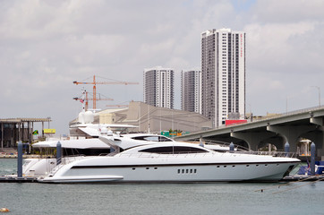 Luxury motor yachts moored at a marina near downtown Miami,Florida with tall buildings and tower cranes in the background.