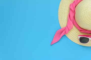 Beach hat, glasses over blue background
