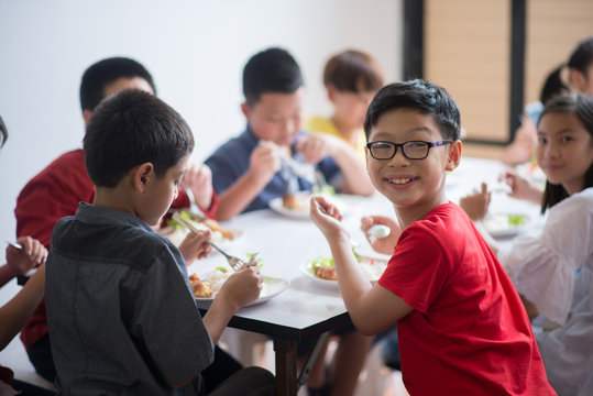 Students boy and girl having lunch time together at school cafeteria