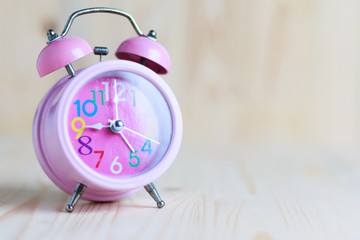 The Pink alarm clock place on the wooden table and wood background