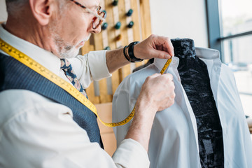 handsome tailor measuring shirt with tape measure at sewing workshop