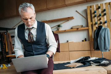 handsome mature tailor working with laptop while sitting on table at sewing workshop