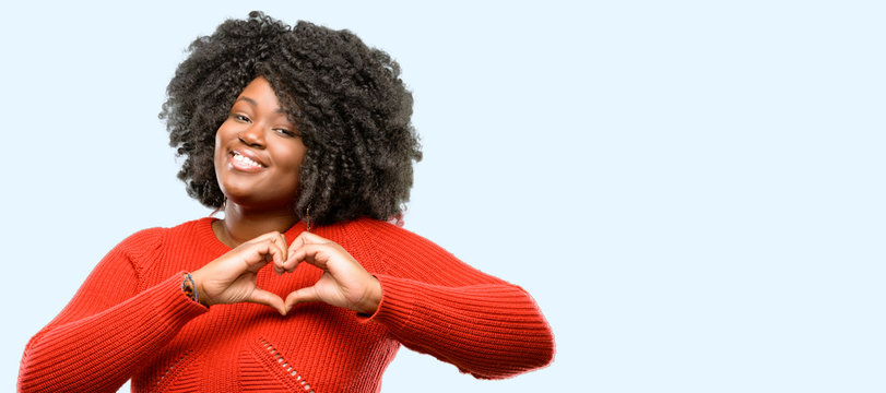 Beautiful african woman happy showing love with hands in heart shape expressing healthy and marriage symbol, blue background