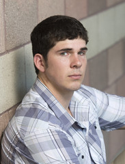 Portrait of young man sitting  against wall with serious facial expression