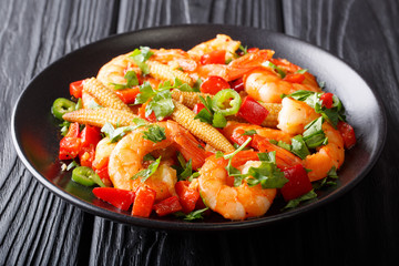 Freshly prepared Mexican prawns with sweet peppers, chili, garlic, corn cobs and herbs close-up. horizontal