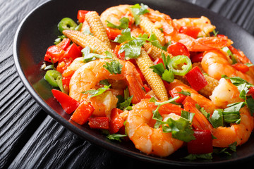 Shrimp with bell pepper, chili, garlic, corn cob and herbs close-up on a plate on the table. horizontal