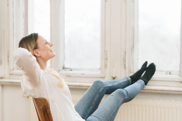 Happy young woman relaxing with her feet up