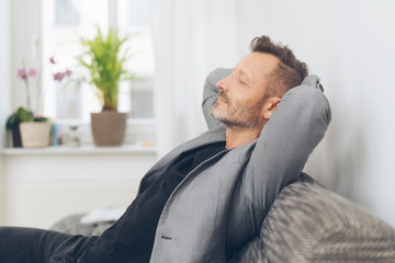 Mature man wearing grey jacket relaxing on sofa