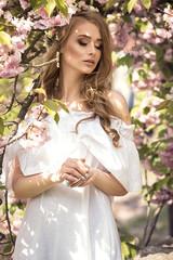Attractive blonde girl in blooming garden.