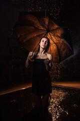 Girl in black dress with umbrella and drops of water