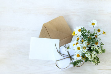 festive set for congratulations/ open envelope with a blank sheet next to a gift and a bouquet of wild flowers top view