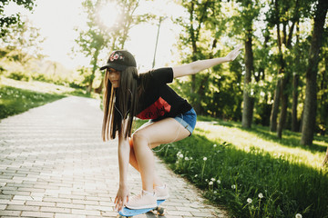 Cute young girl skateboarding in the park while listening music in headphones.