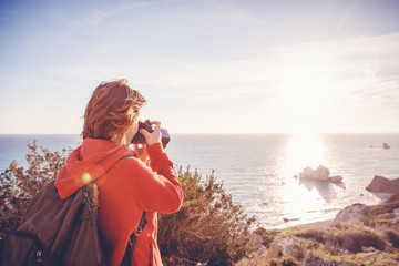 young woman traveler with a camera stands on a rock and looks at the horizon, freedom, summer travel, profession, freelancer, journalist, blogger, professional photographer