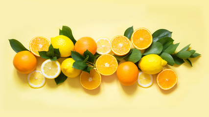 Summer set of tropical fruits, lemon, orange and green leaves on yellow. Banner.
