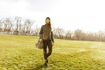 Picture of young handicapped girl with prosthetic leg in sportswear, walking on grass in sunny day