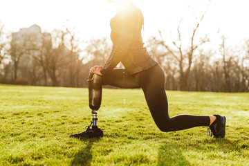 Cropped image of disabled athletic girl in black sportswear, doing lunges and stretching prosthetic leg on grass