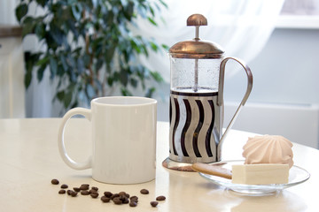 Coffee mug mockup in the kitchen interior. White ceramic cup on the table with a french press and some dessert