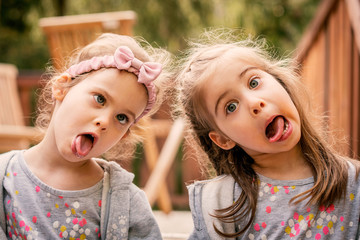 two adorable girls are sitting on the stairs and making funny faces