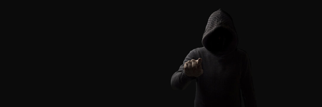 Faceless man in a hood with points a finger at the viewer on a dark background. Concept Threats and Terror
