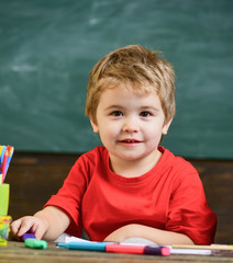 Little boy sitting in the classroom. Blond cute kid holding purple marker.