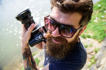 Man with beard and mustache wears sunglasses, water surface on background. Guy shooting nature near river or pond. Hipster on smiling face holds old fashioned camera. Tourist photographer concept.