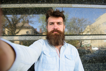 Vlogging concept. Hipster, tourist with tousled hair and long beard looking at camera, taking selfie photo. Man, tourist with beard and mustache on calm, serious face, black marble background.