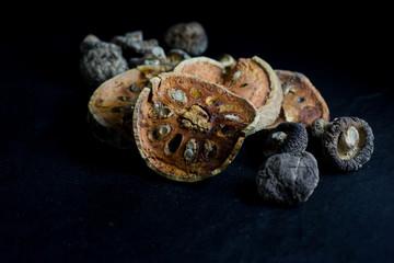 Dry bael fruit tea and  Mushroom isolated on black background