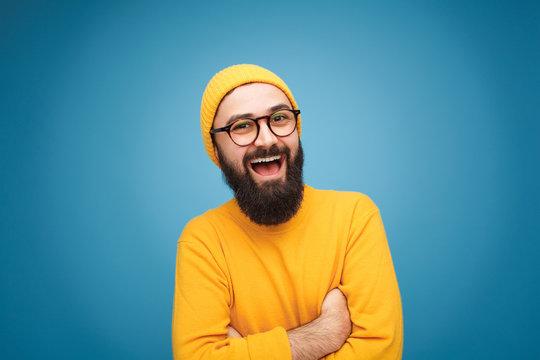 Smiling trendy guy on blue background