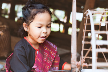 Cute asian child girl in Thai traditional dress using traditional wooden spinning wheel with fun and curious