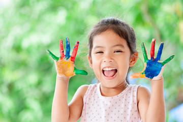 Cute asian little child girl with painted hands smiling with fun and happiness on yellow nature background