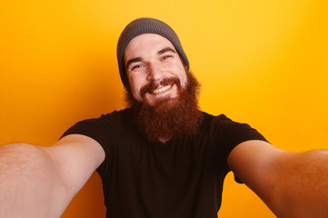 Smiling bearded man taking a selfie over orange background