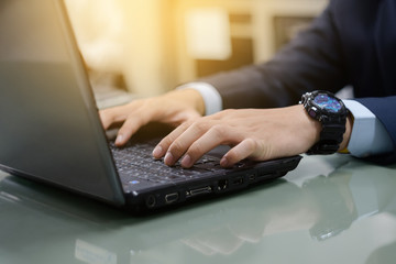 Close up of business person's hands using laptop on table in the office. Close shot of office workers using laptop in the office.