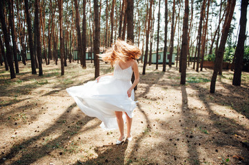 sexy bride runs in her dress in forest