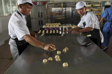 Workers work on dough for rose pastries at a factory that makes flower pastries, in Kunming