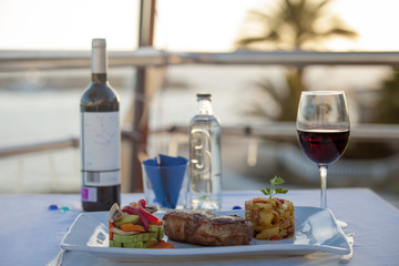 table in a restaurant on the background of the ocean. meat with garnish in a restaurant