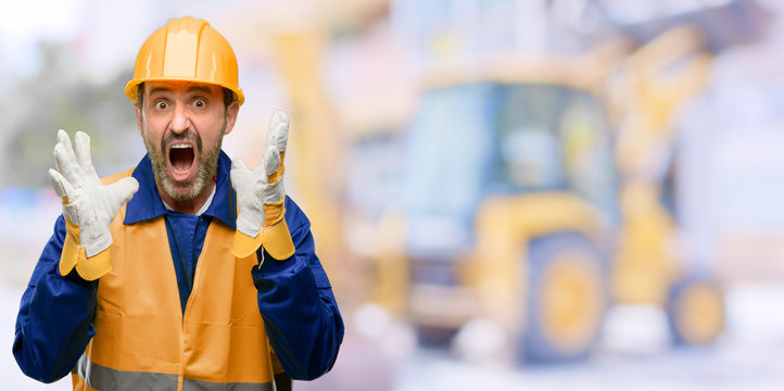Senior engineer man, construction worker stressful keeping hands on head, terrified in panic, shouting at work