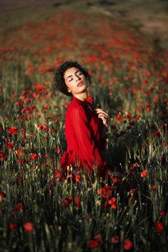 Gorgeous model in red dress holding poppy flowers