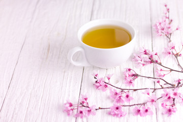 A cup of tea and blossomed cherry tree branch, using white wooden table. Slightly pink shades.