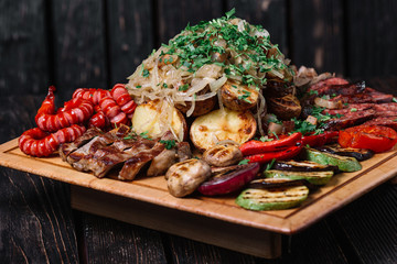 Assorted delicious grilled meat, sausages and vegetables on cutt