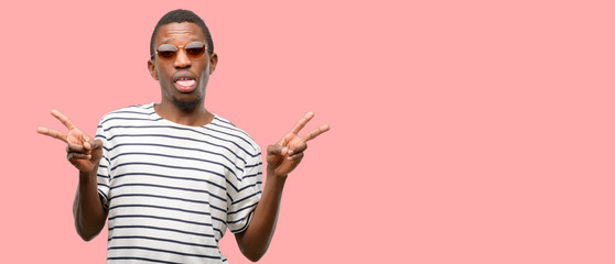 African black man wearing sunglasses looking at camera showing tong and making victory sign with fingers