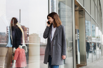 Young beautiful woman walking along the street talking via mobile phone and doing shopping, stylish girl looking at clothes shop window while having a conversation with friend on smartphone