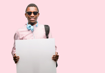 African black man student holding blank advertising banner, good poster for ad, offer or announcement, big paper billboard
