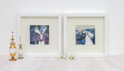 White interior display. Two drawings of hares on collaged blue backgrounds in frames. With egyptian glass scent bottles, and cherry blossom on a shelf.