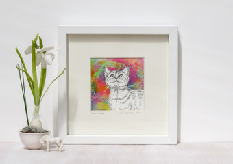 White interior display. Drawing of smiling cat on a vibtant colourful collaged background in a frame. With a snowdrop on a shelf.