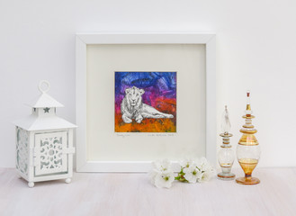 White interior display. Drawing of lion on a colorful collaged background in frame. With egyptian glass scent bottles, tea light and cherry blossom.